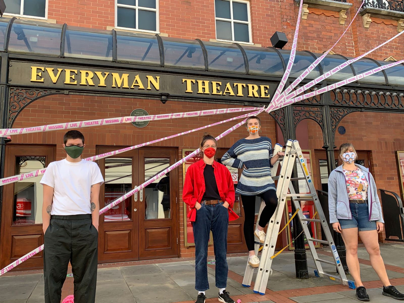From l to r: Jacob Lucy, Lauren Dix, Dora Furnival and Lucy Fowler from Scene Change wrap the Everyman Theatre, Cheltenham in decorative #missinglivetheatre ribbon.